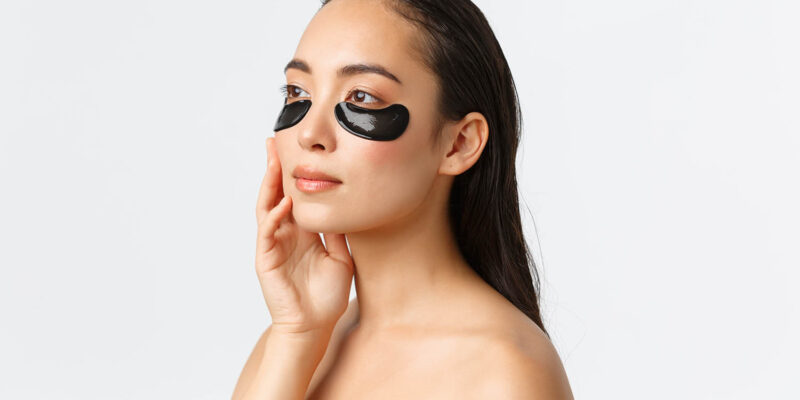 Attractive sensual woman using eye patches