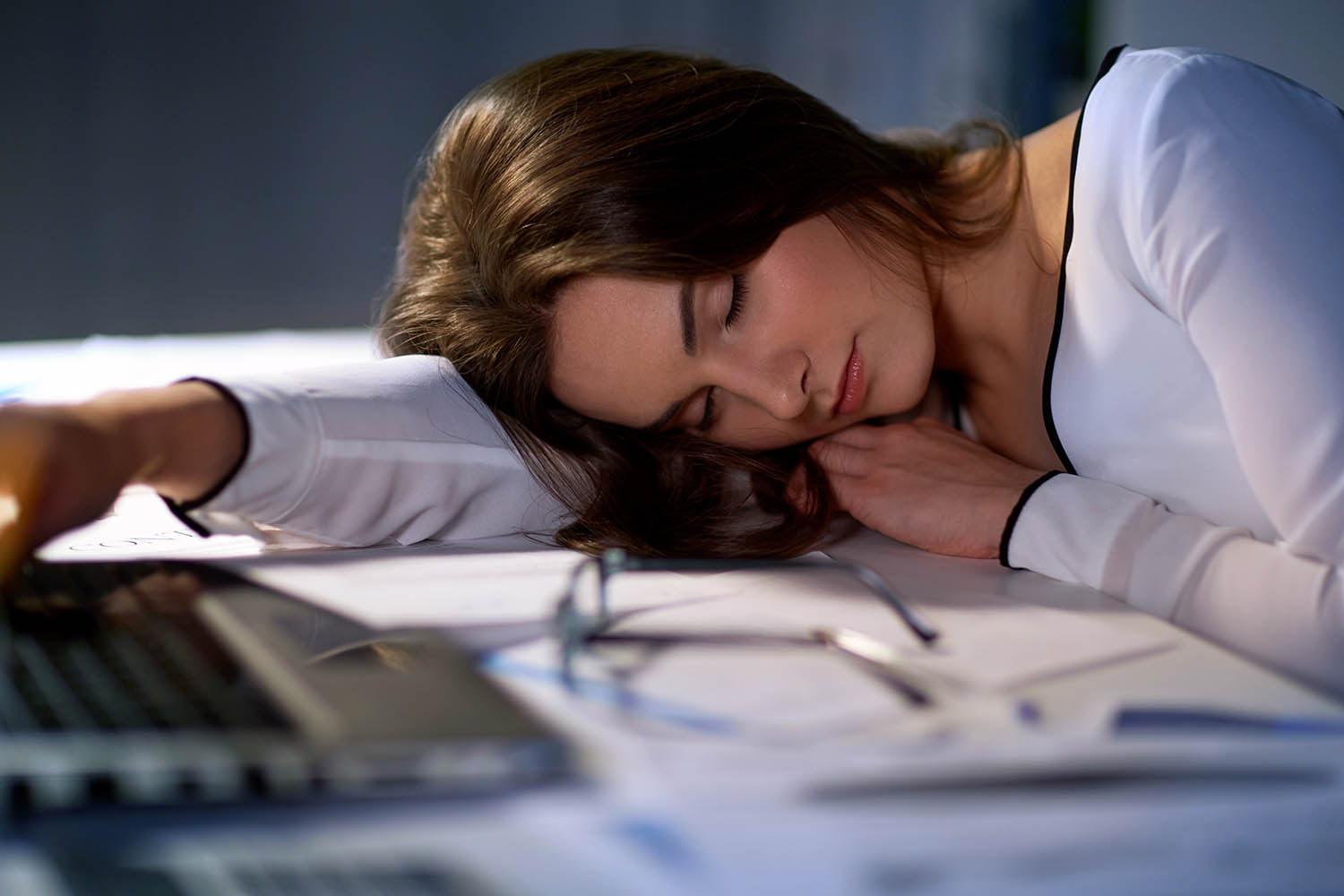 Tired woman sleeping on office table