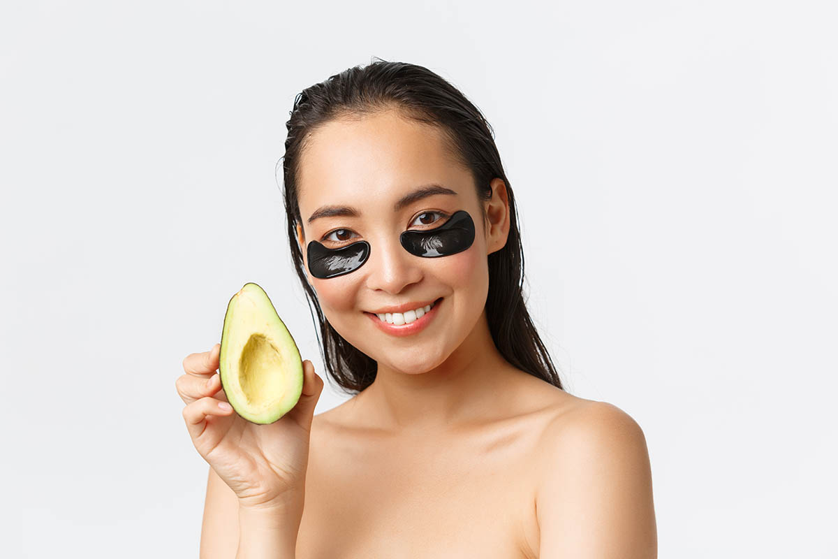 woman trying avocado for home remedy swollen eye bags