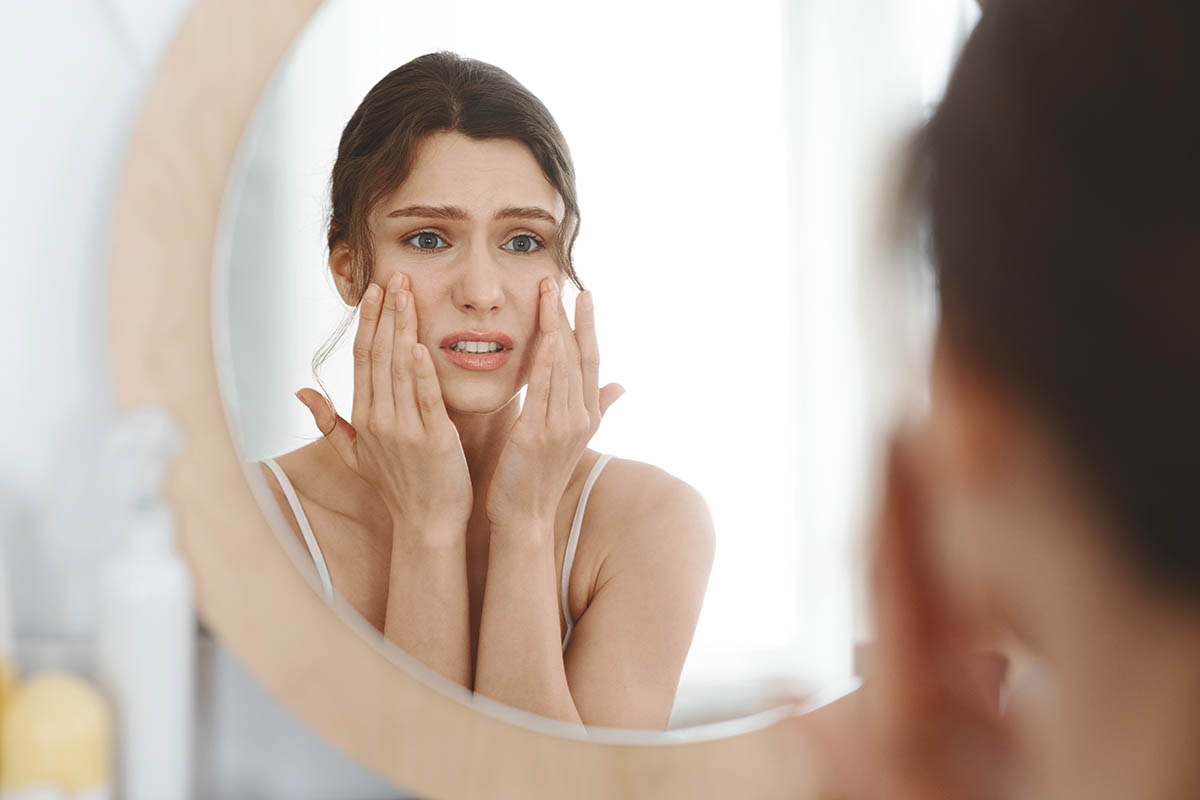 Stressed girl touching her eye bags and looking at mirror