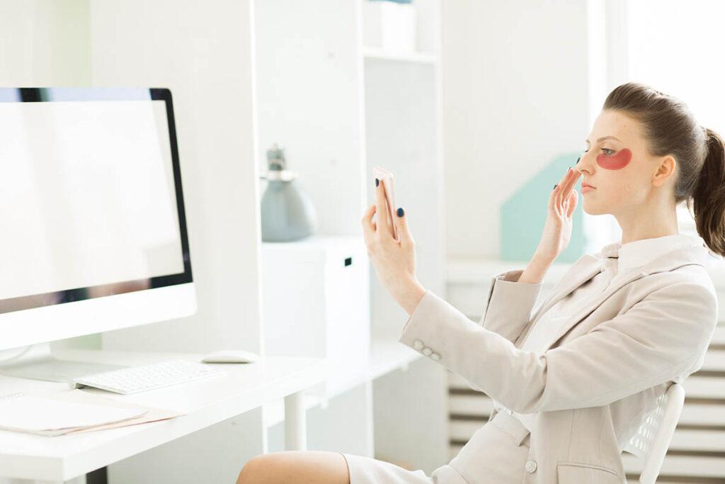 woman applying under eye mask