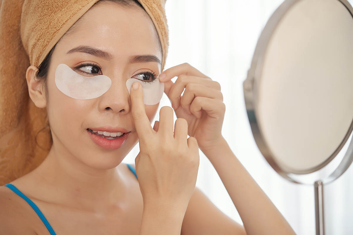 Young woman applying under eye patches for puffy eyes